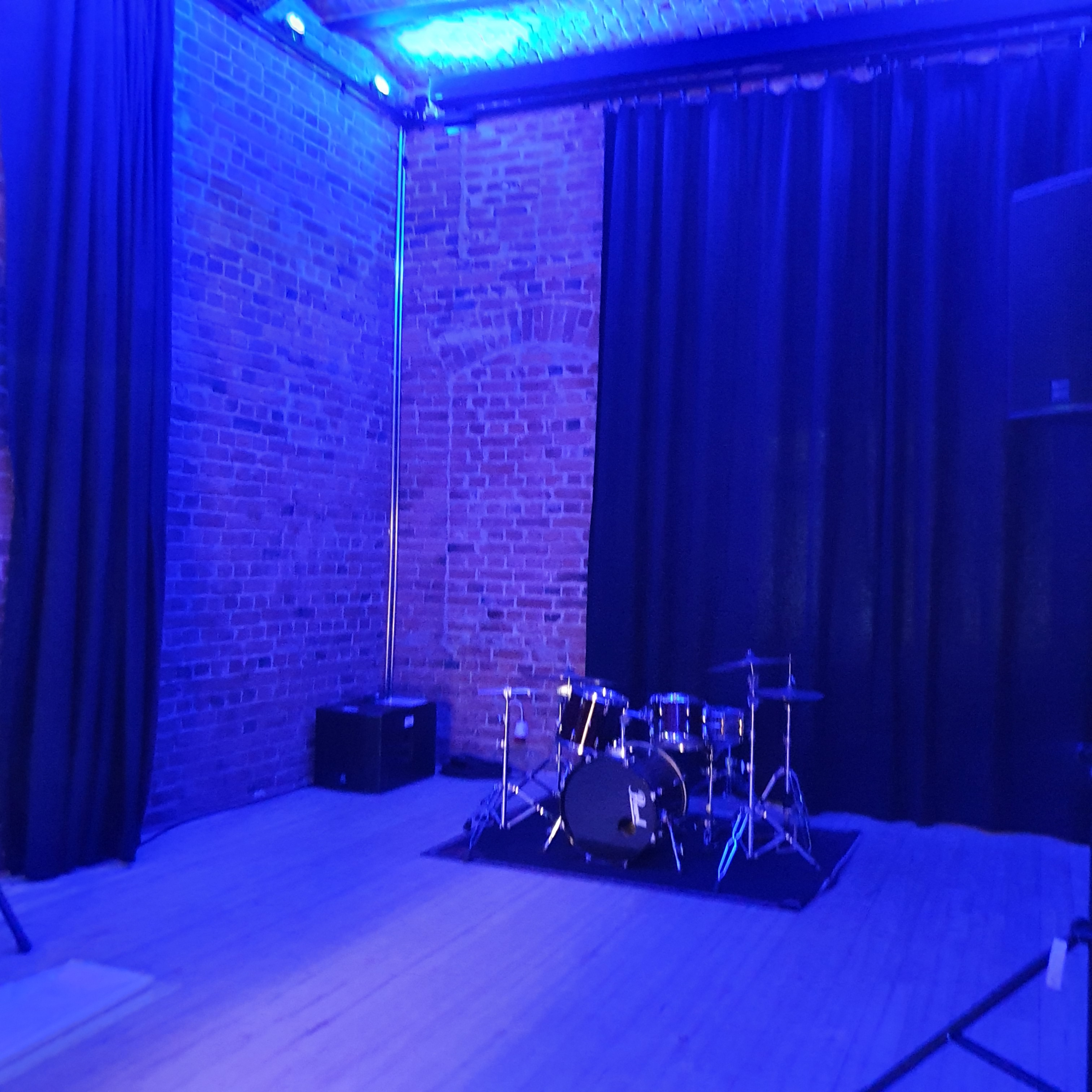Drum kit set up in front of red brick wall in Kammio bathed in blue light