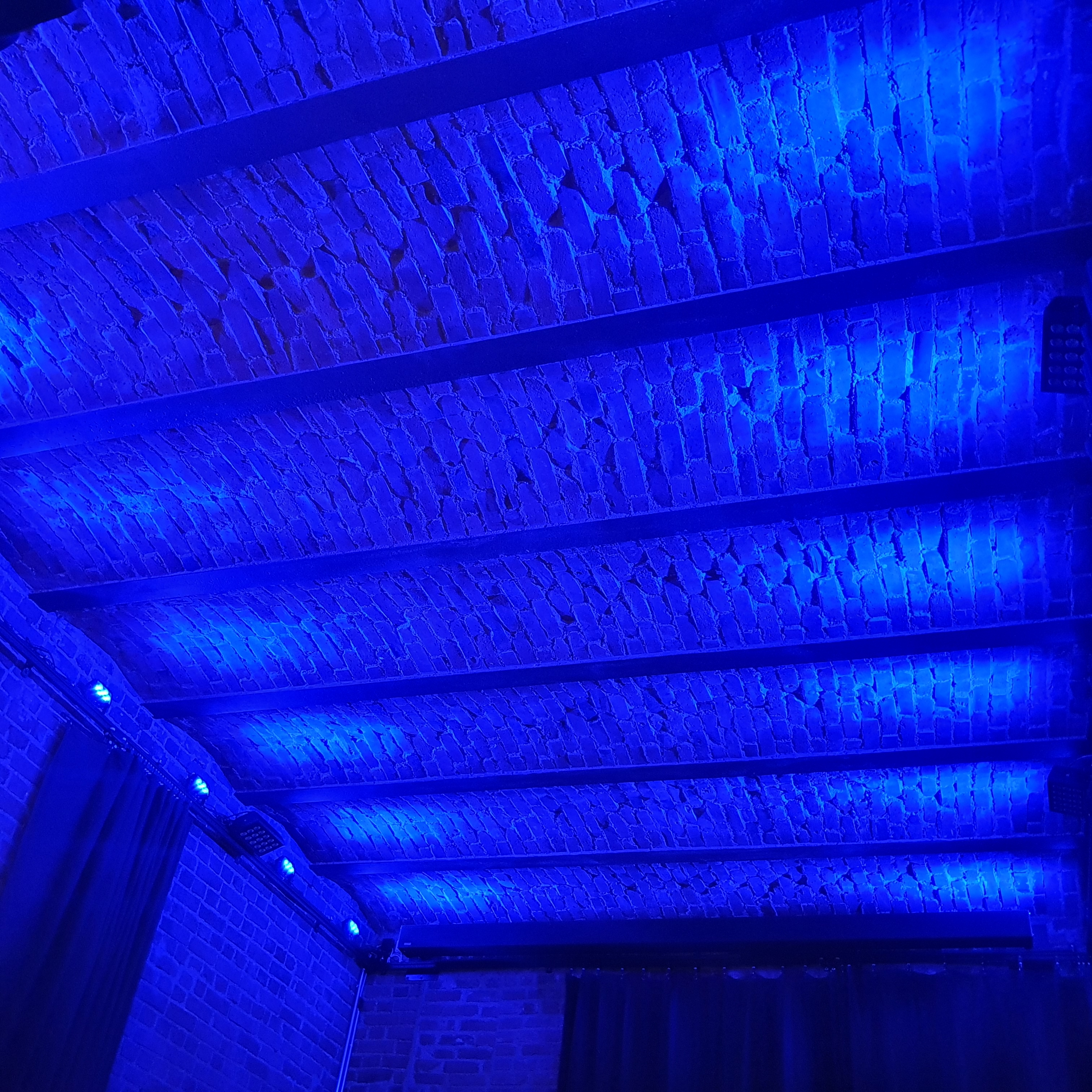 Red brick ceiling with steel railway track girders in Kammio bathed in blue light