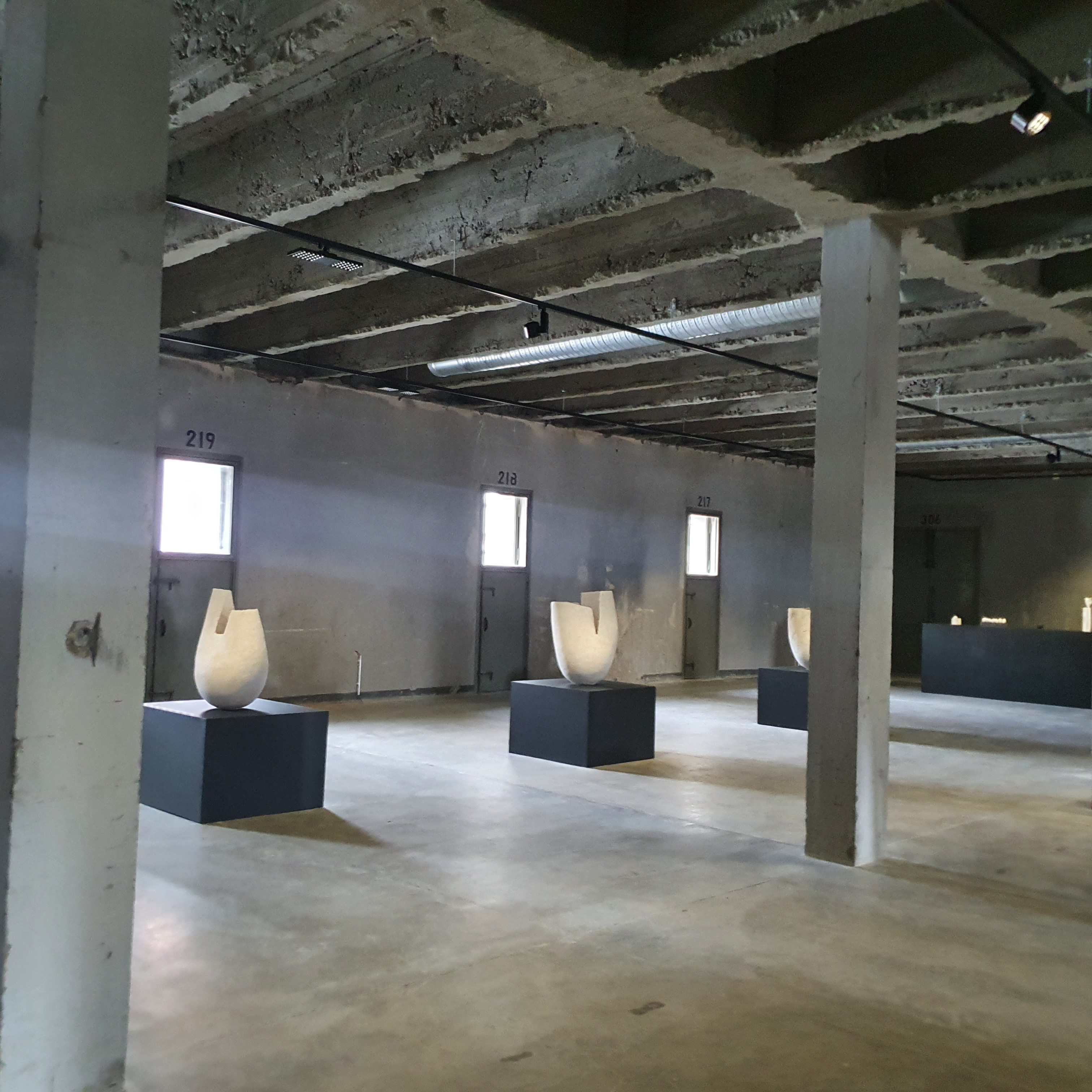 Three large white urns/vases in a bare, concrete room. Calix exhibition by Päivi Rintaniemi
