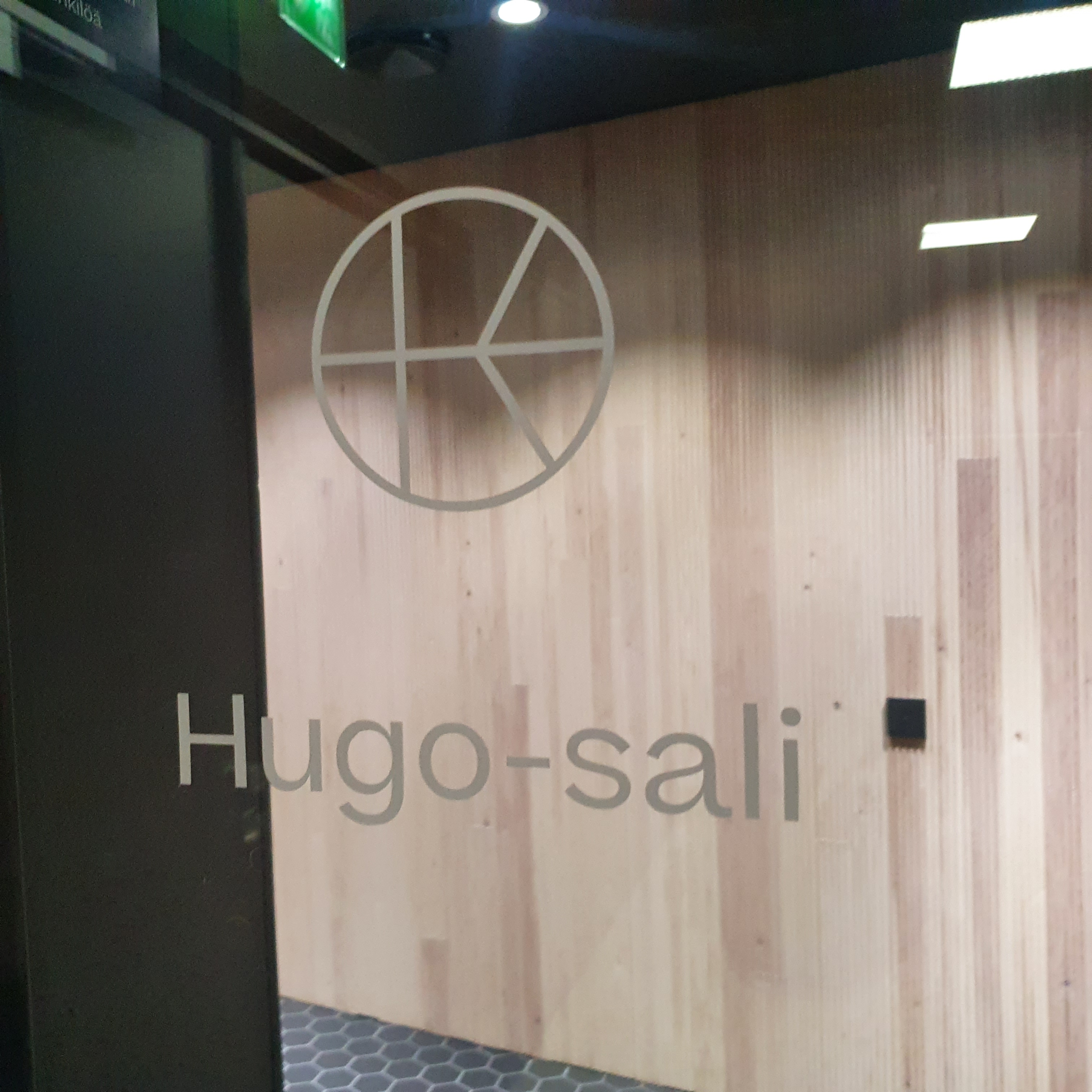 Glass door with a white logo reading Hugo sali