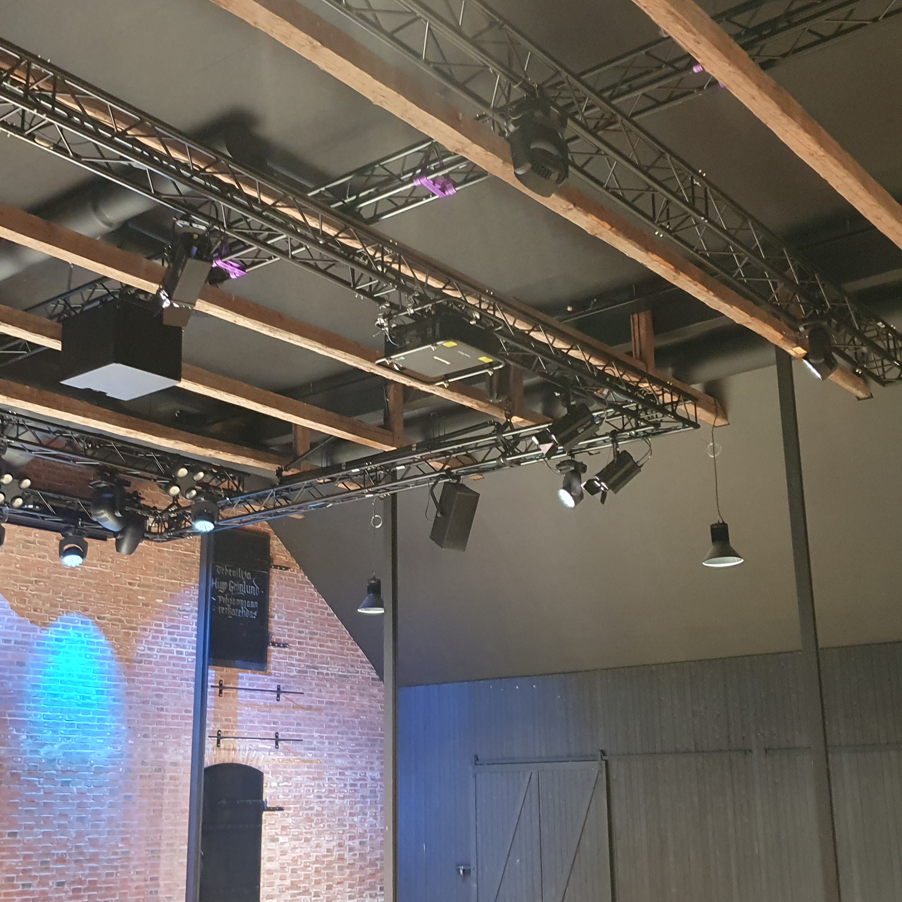 Light wood coloured beams against a black ceiling. In the background is a red brick wall and a black wooden wall