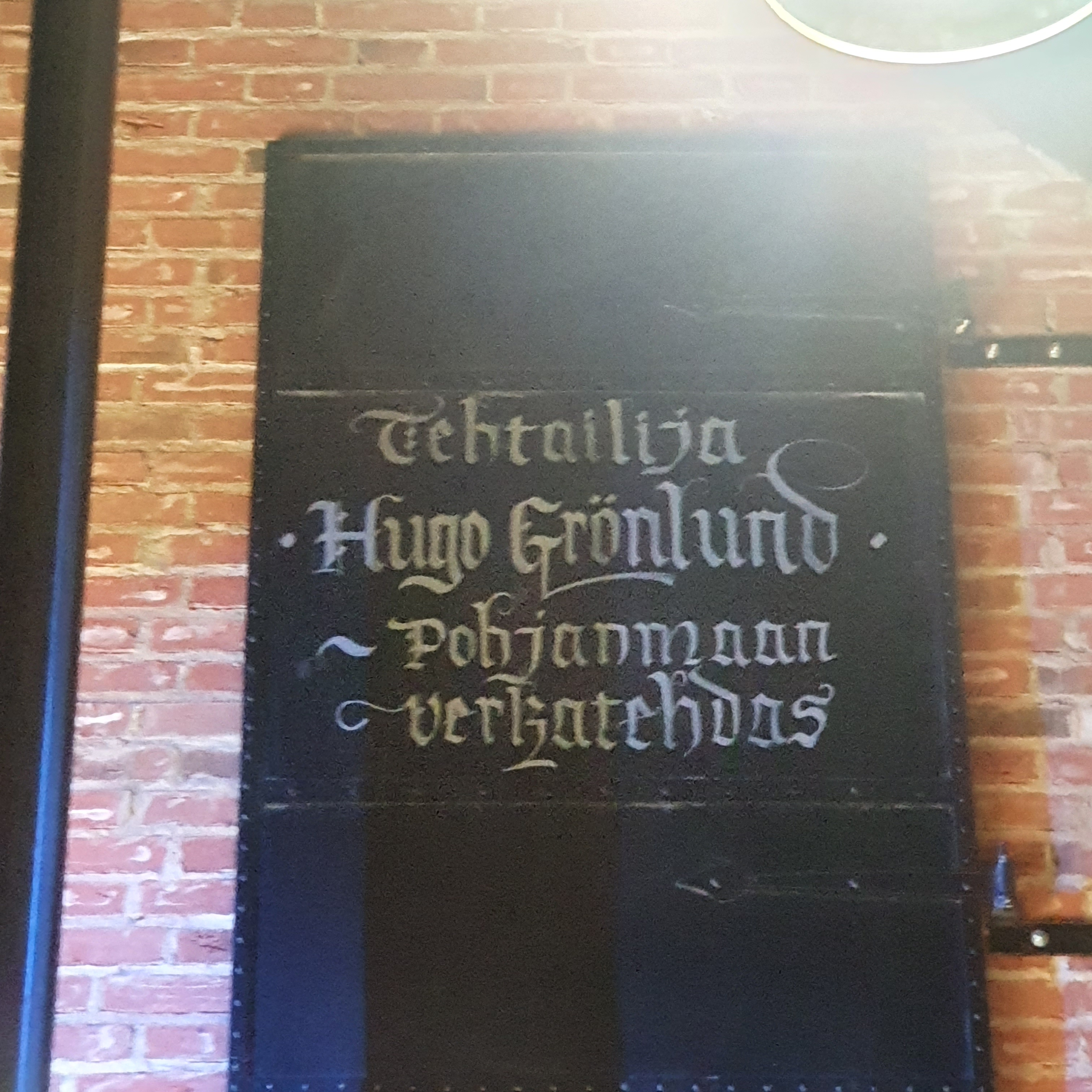 Black door in a red brick wall with the name Hugo Grönlund in white script