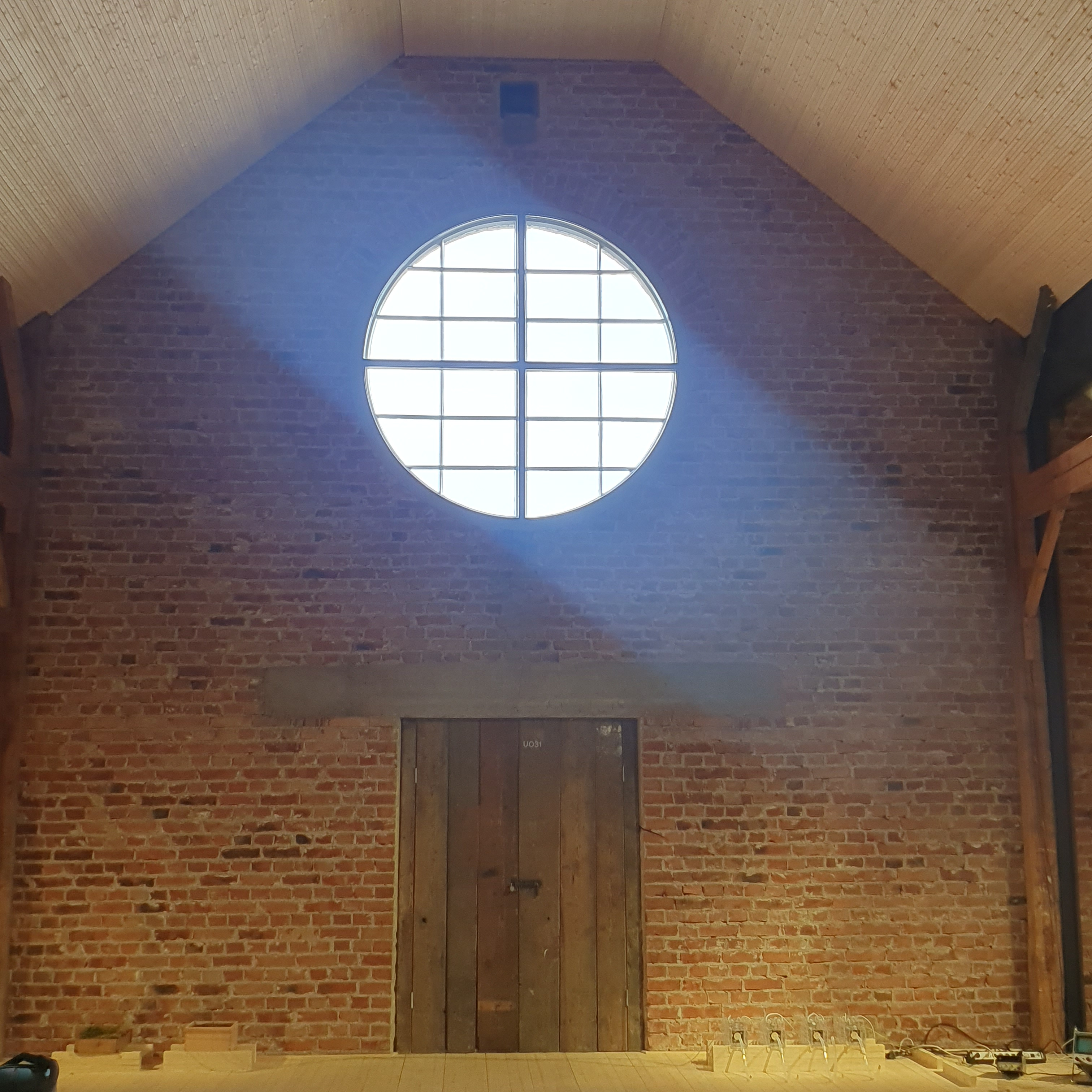 Large round window with light pouring through it, set into a red brick wall
