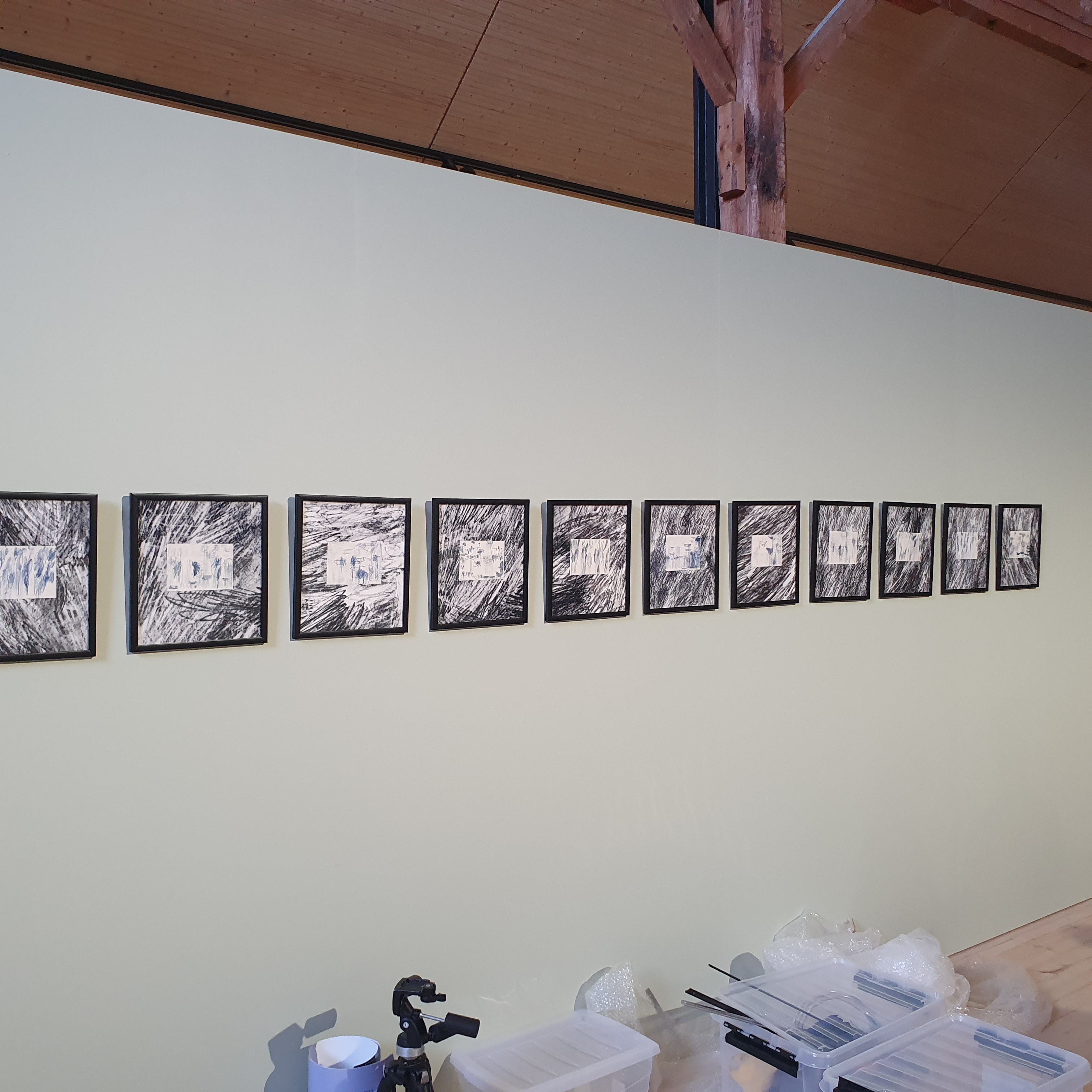 """A row of pictures from the """"Stump of Prometheus – Stay together"""" exhibition hung on the wall in black frames"""