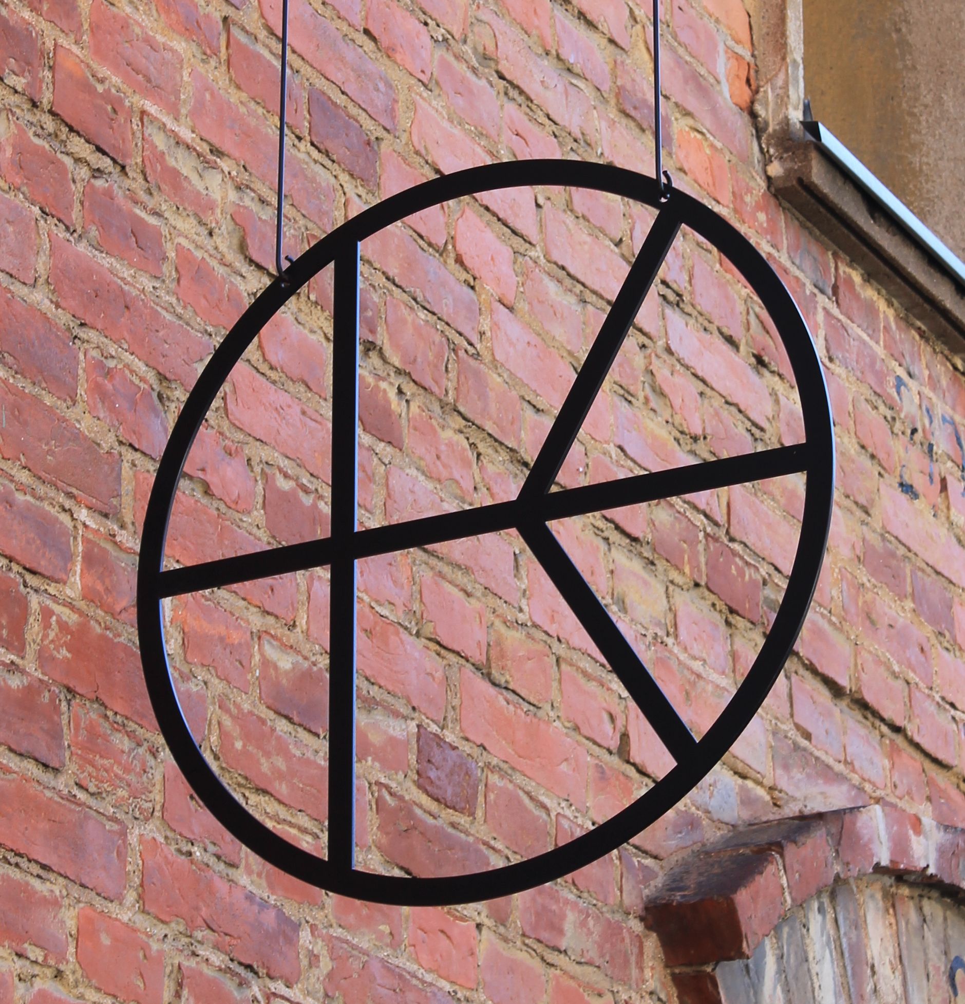 Black metal hanging sign of Kalevan Navetta logo, inspired by the round window in Vintti